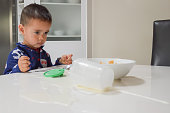 A candid photograph of a 2-year old Eurasian boy having breakfast in his pyjamas, and upset over spilling his cup of milk on the table