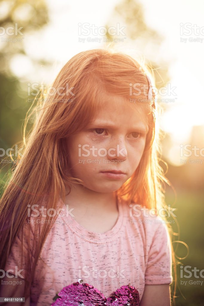 Crying redhead girl in park expressing disappointment and anger stock photo