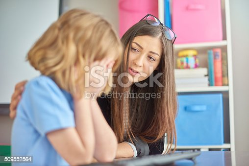 a primary school girl is sitting at her computer desk in school and crying into her hands . Her young teacher looks on  in the background , puts her arm around her and gives support .
