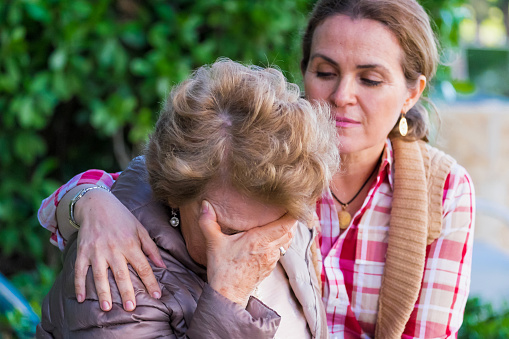 istock Crying senior woman holding her face being comforted 498196062