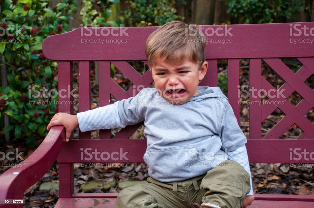 Crying Toddler on Bench stock photo