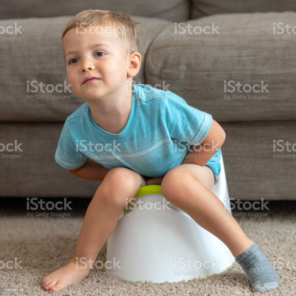 crying toddler sitting on his portable toilet at his home stock photo