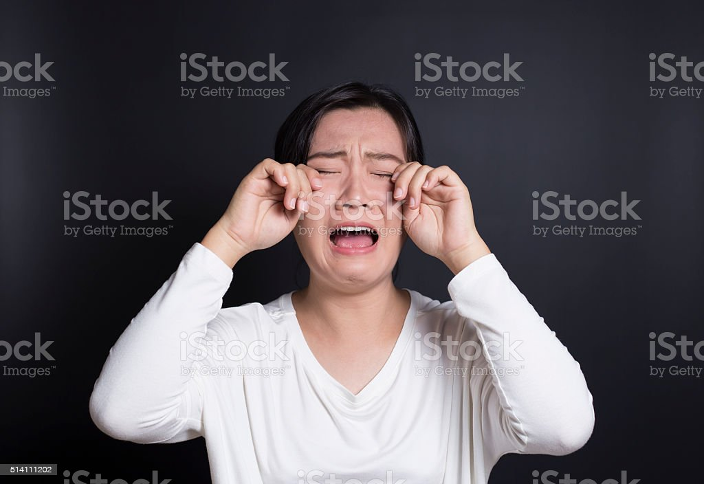 Crying Woman on Black Background stock photo