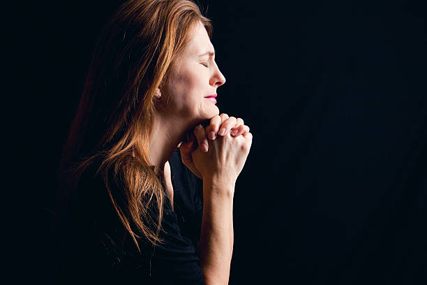Crying Woman Praying A sad woman crying as she prays. woman crying stock pictures, royalty-free photos & images