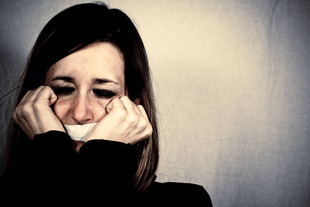 Crying Woman with Tape Covering Mouth stock photo