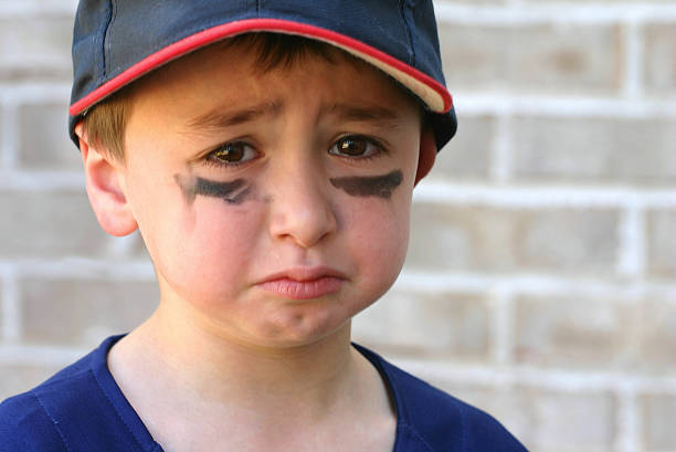 Crying young boy with black marks on his face stock photo