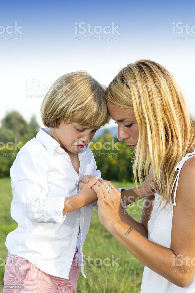 Crying young boy showing finger injury to his concerned mother,...