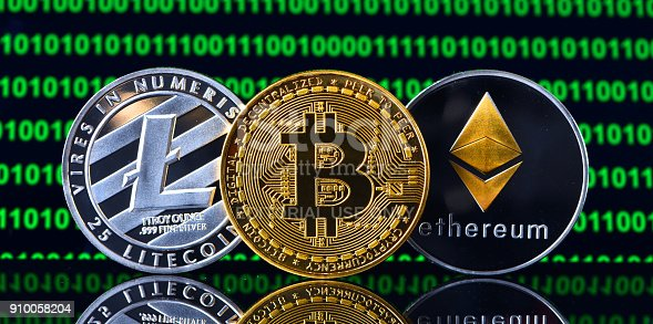 İstanbul, Turkey - January 24, 2018: Close up shot of memorial coins of bitcoin, litecoin and ethereum on a screen displaying binary code . Bitcoin, Litecoin and Ethereum are  crypto currencies and a worldwide payment systems.ethere
