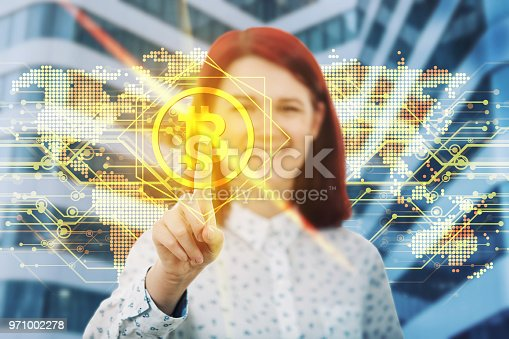 Smiling woman touching digital screen interface. Press on the golden bitcoin icon over world map hologram background. Modern technology, virtual cryptocurrency concept distributed ledger.