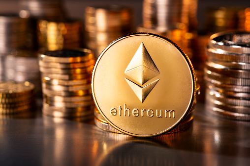 Frankfurt, Hesse, Germany - April 12, 2018: Cryptocurrency coin Ethereum with several stacks of coins in the background