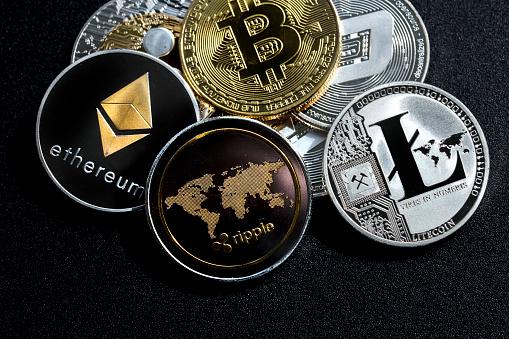 izmir, Turkey - September 28, 2018 Close up ethereum ripple litecoin bitcoin dash coins shot in metallic black background in studio