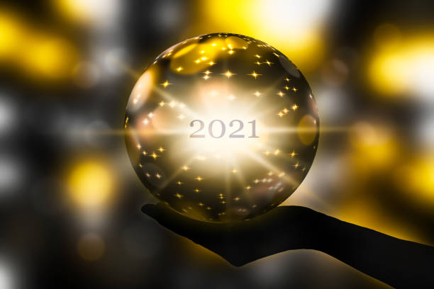 crystal ball in a hand, prediction for new year 2021 on abstract shiny blurred background crystal ball in a hand, prediction for new year 2021 on abstract shiny blurred background forecasting stock pictures, royalty-free photos & images