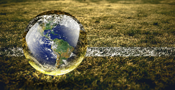 Crystal ball reflecting globe of the earth in nature