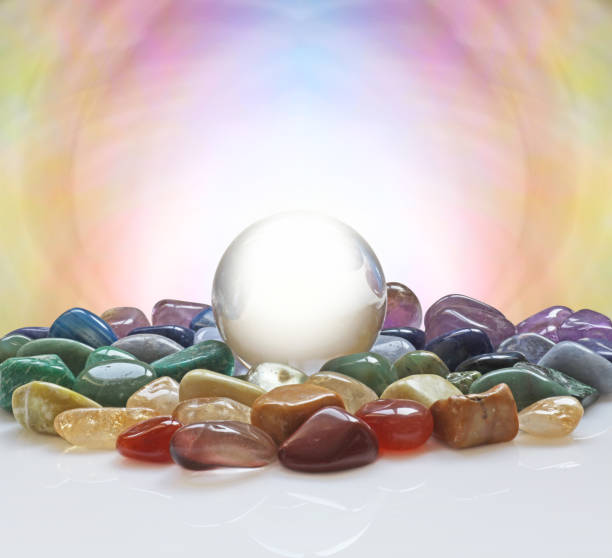 Crystal ball surrounded by healing crystals Large clear crystal ball with a selection of chakra coloured healing crystals and a pastel coloured background plus plenty of copy space crystal healing stock pictures, royalty-free photos & images