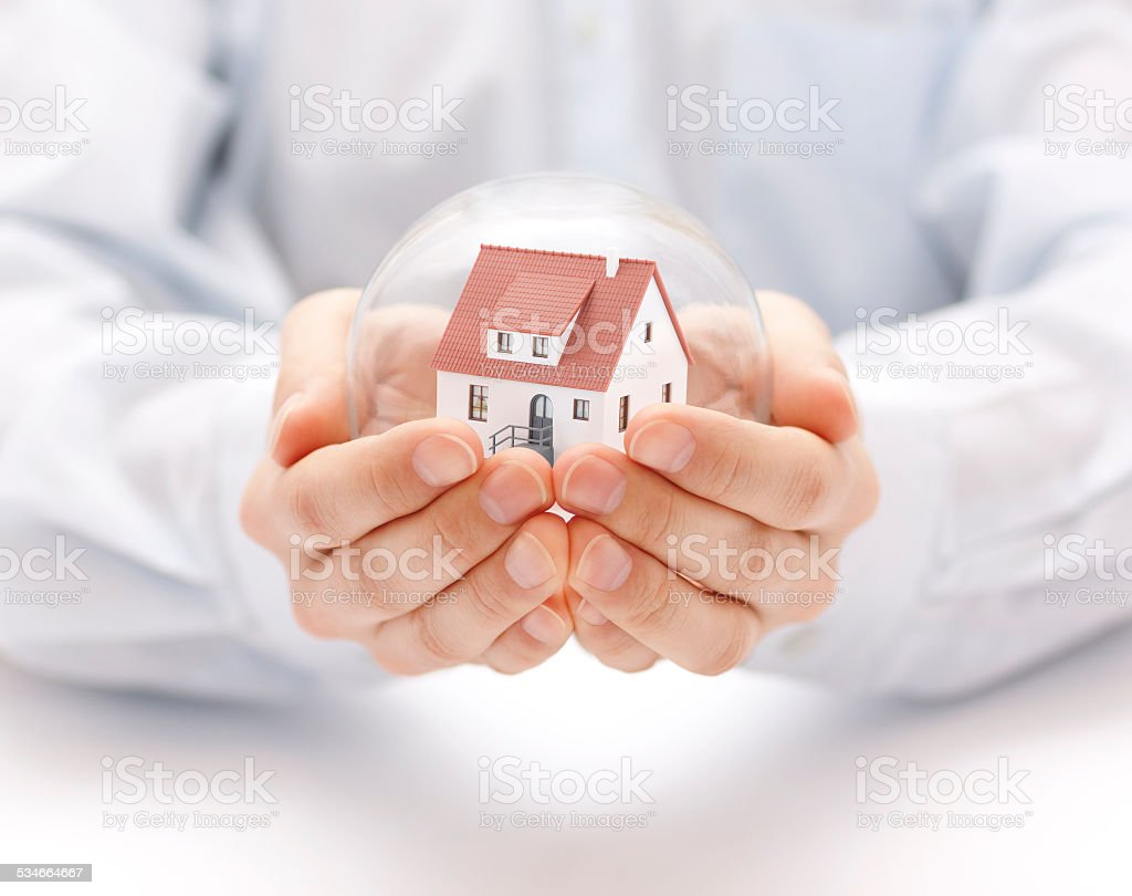 Crystal ball with house in hands stock photo