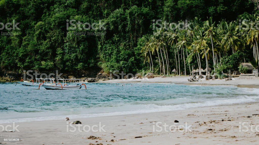 Crystal Bay, Palm trees on sandy beach with some local boats in ocean. Nusa Penida Bali stock photo