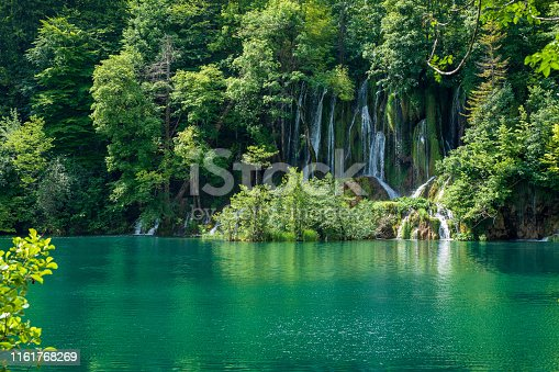 Waterfalls splashing down an overgrown rock face at the Plitvice Lakes National Park. Plitvička Jezera, Croatia - June 25th 2019 - Official photography permission obtained by the Plitvice Lakes National Park and available on request.