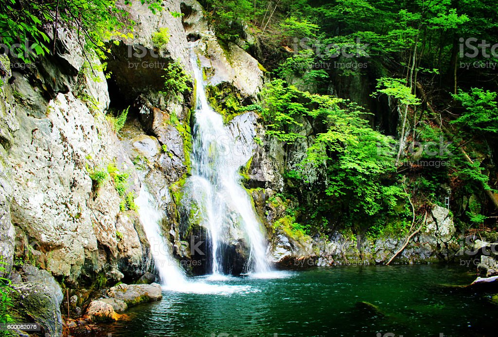 Crystal clear waterfall hidden in mountains stock photo