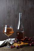 A crystal glass full of rose wine, next to a bottle and a bunch of red ripe fresh grapes. Vertical orientation. Place for text.