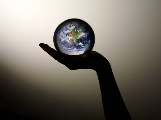 Crystal Globe of the World in your Hands stock photo