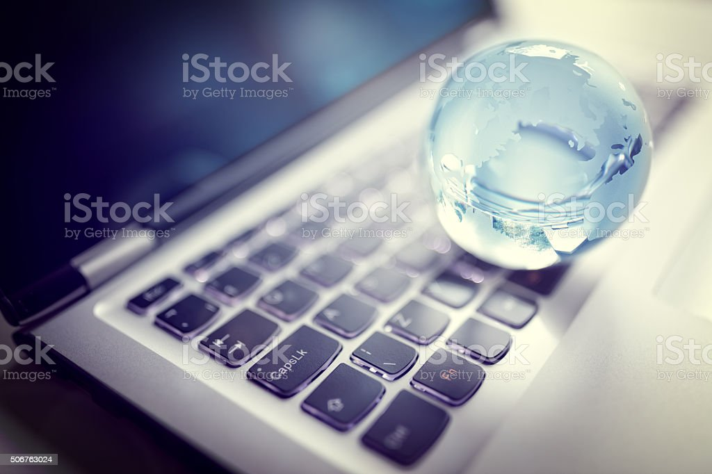Crystal globe on laptop keyboard Glass crystal globe on laptop keyboard concept for global communication and business Blue Stock Photo