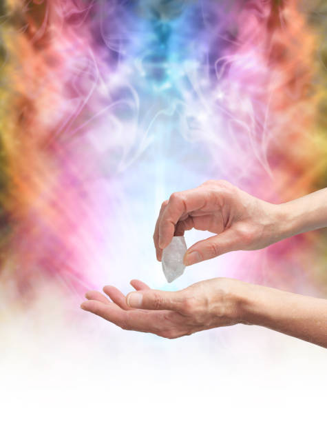 Crystal healer sensing energy with terminated quartz Crystal Healer holding terminated quartz in one hand pointing it at open palm with psychedelic rainbow coloured energy formation in background crystal healing stock pictures, royalty-free photos & images