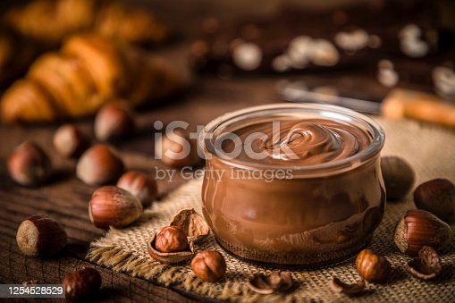 Front view of a crystal jar full of chocolate and hazelnut spread surrounded by some hazelnuts on a rustic wooden table. Selective focus is on the jar and on the defocused background are some croissants and chocolate bars. Predominant color is brown. Low key DSLR photo taken with Canon EOS 6D Mark II and Canon EF 24-105 mm f/4L