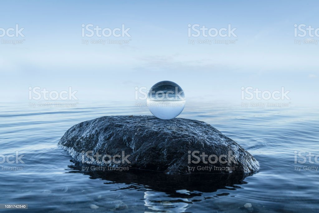 Crystal orb on a black rock by the blue ocean stock photo