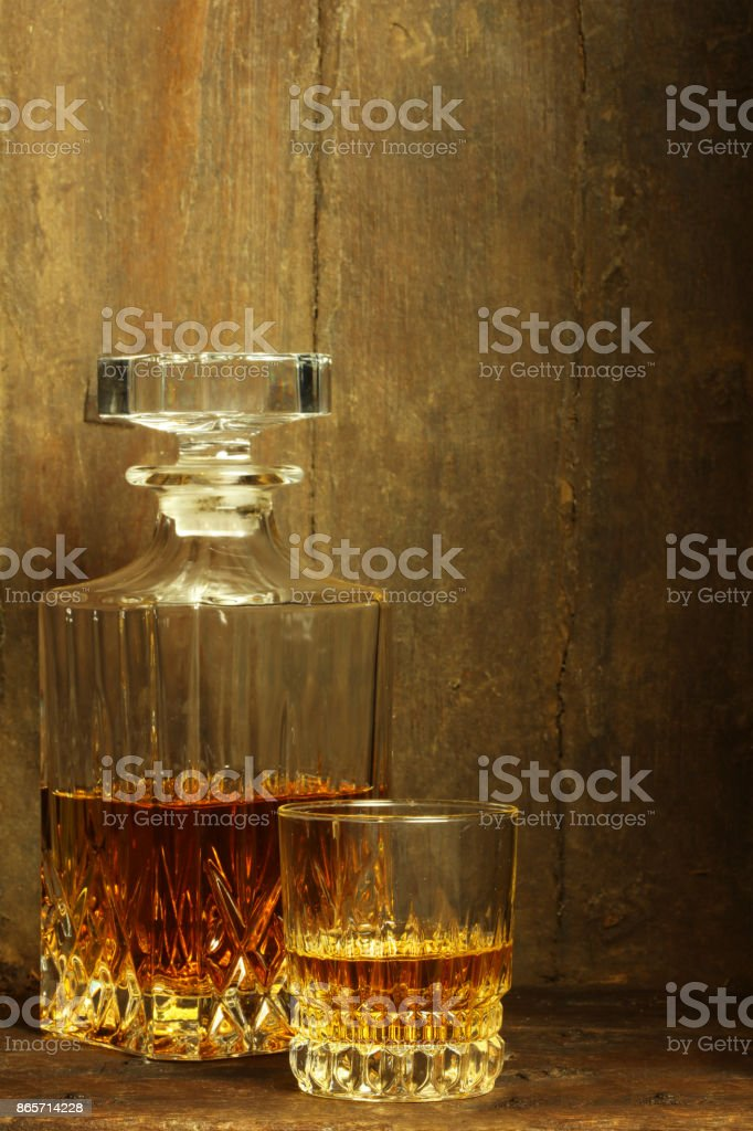 Crystal Whiskey Decanter and Glass on Rustic Background stock photo