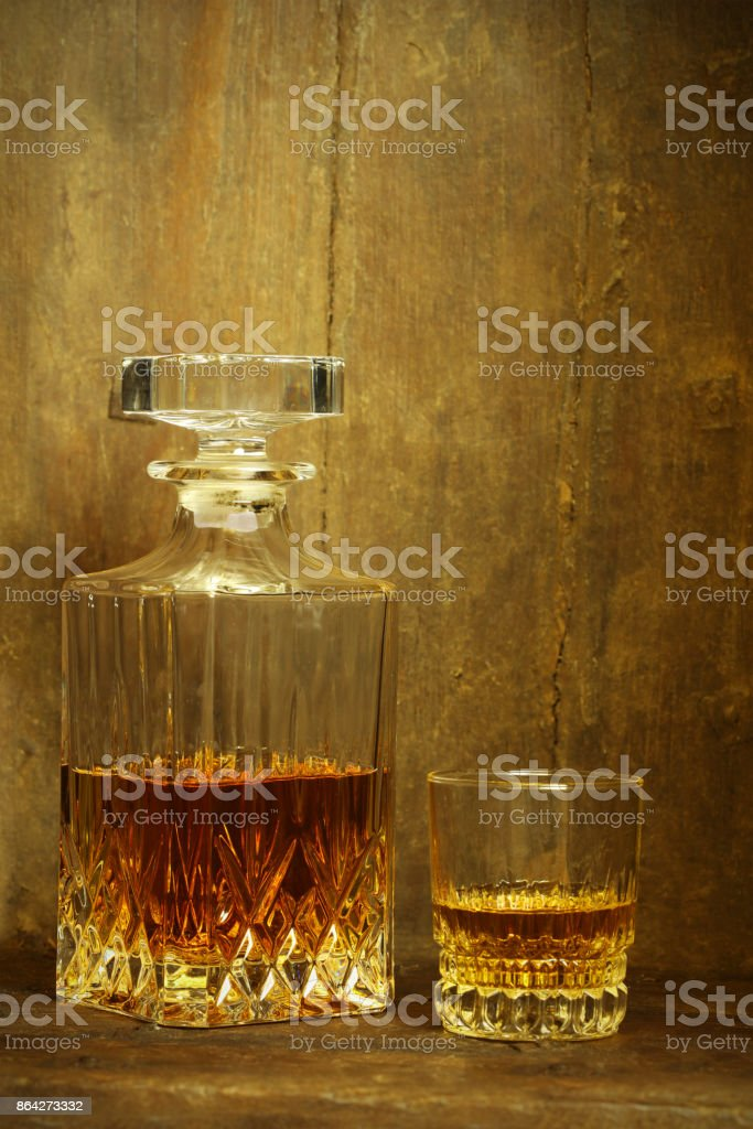 Crystal Whisky Decanter and a Glass Against Rustic Background royalty-free stock photo