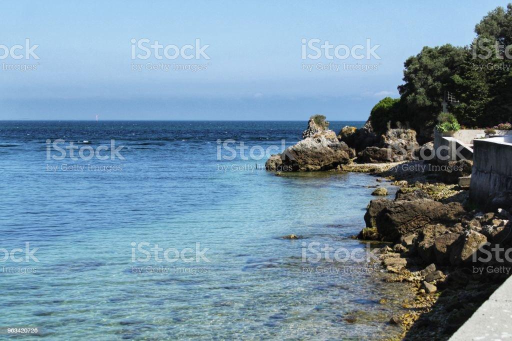 Krystaliczne wody plaży Portinho w Lizbonie - Zbiór zdjęć royalty-free (Atmosfera - Wydarzenia)