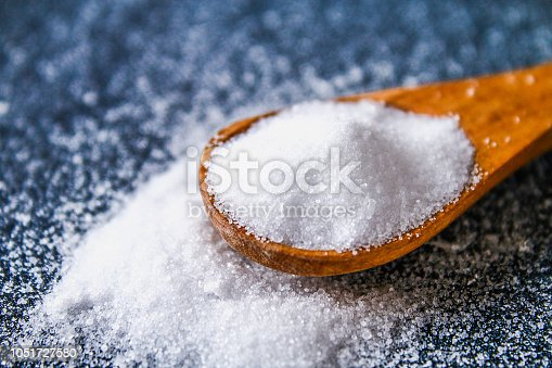 Crystals of shallow salt in a scoop, spoon on a dark gray table. Background for advertising salt. Table salty. Salted food