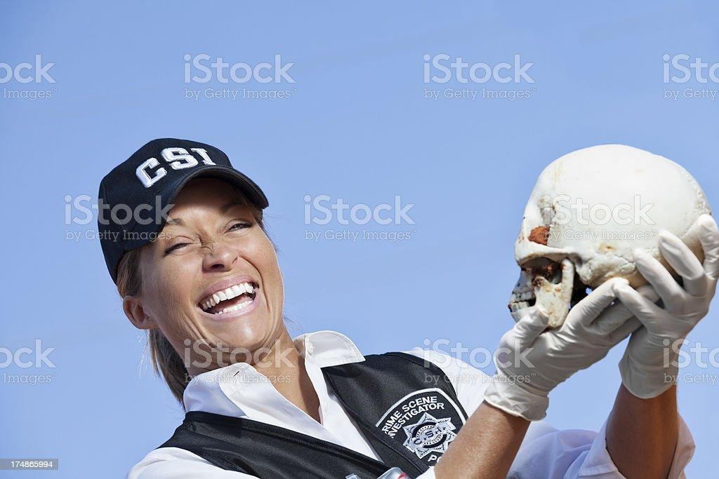 Female crime scene investigator laughing while holding a skull....