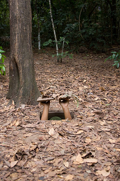 Cu Chi Tunnels Entering one of the original, unwidened entrances to the Cu Chi tunnel system, near Saigon  viet cong stock pictures, royalty-free photos & images
