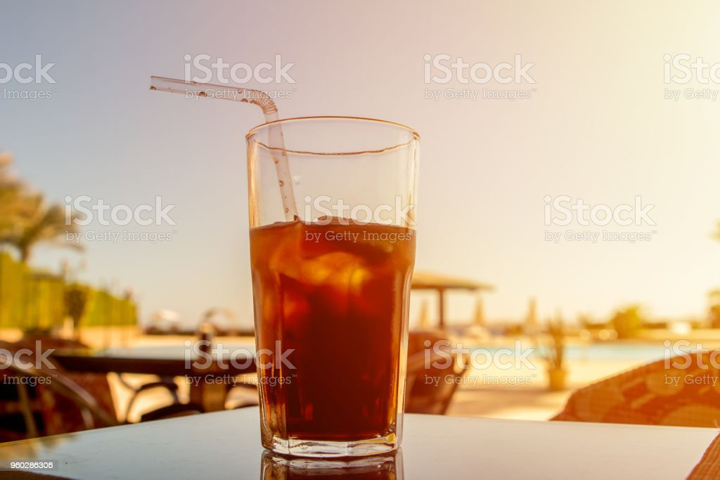 Cuba Libre cocktail and ice in glass sunrise stock photo