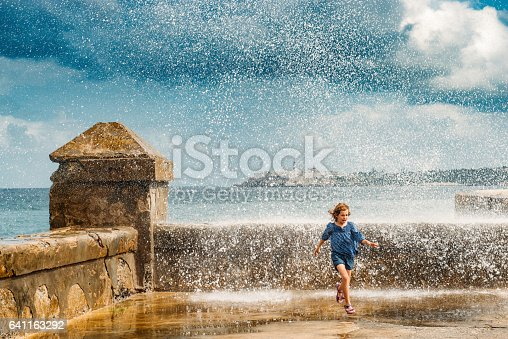 Little girl running away from the waves crashing on Havana's Malecón. Cuba.