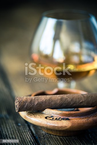 cuban cigar in ash tray and cognac or rum