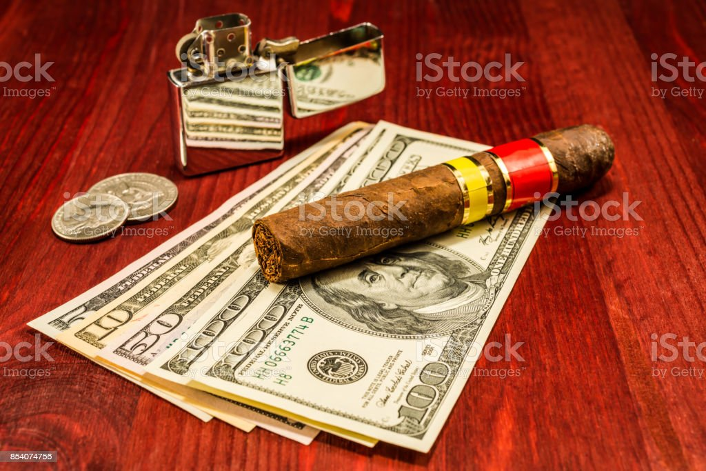 Cuban cigar on a several dollar bills and also coins and lighter stock photo