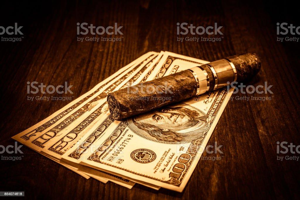 Cuban cigar on a several dollar bills on the table stock photo