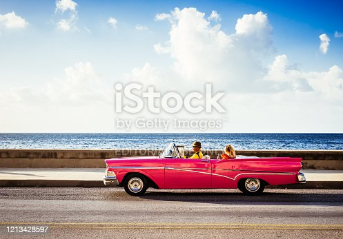 Havana ,Cuba - October 04, 2018: Cuban driver takes a tourist on a city tour in a american red convertible vintage car on the promenade Malecon in Havana City Cuba - Serie Cuba Reportage