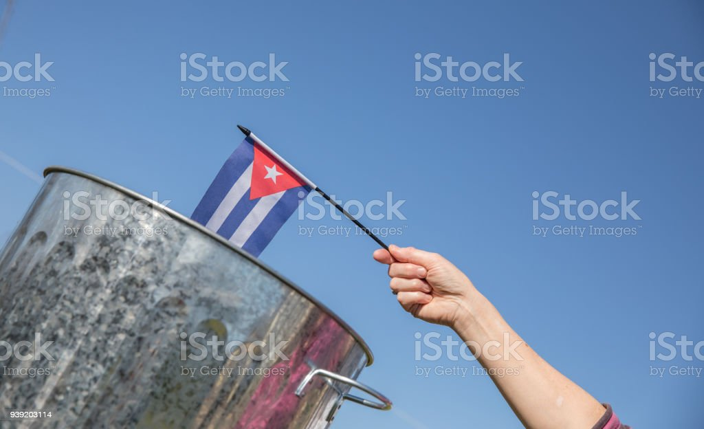 Cuban flag being placed into a dustbin stock photo