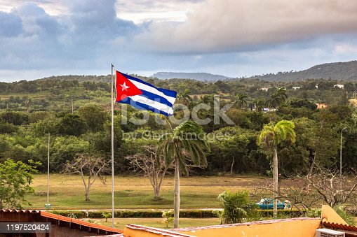 Cuban flag floating in the countryside of Cuba