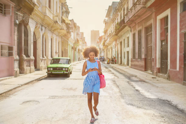 Cuban girl looking at mobile phone, walking down street in Havana stock photo