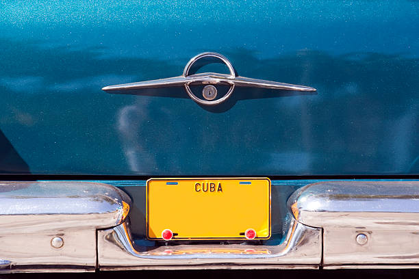 Cuban Licence Plate Blank yellow Cuban vehicle licence plate on old American car bumper stock pictures, royalty-free photos & images