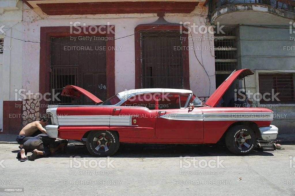 Cuban Men Fix Vintage Red American Car on Street royalty-free stock photo