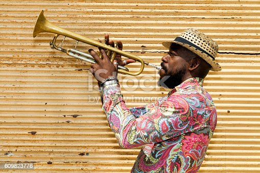 A well known professional Cuban musician with a beard, wearing a Panama hat, standing against a closed yellow store shutter, playing a trumpet outdoors, Havana, Cuba, 50 megapixel image