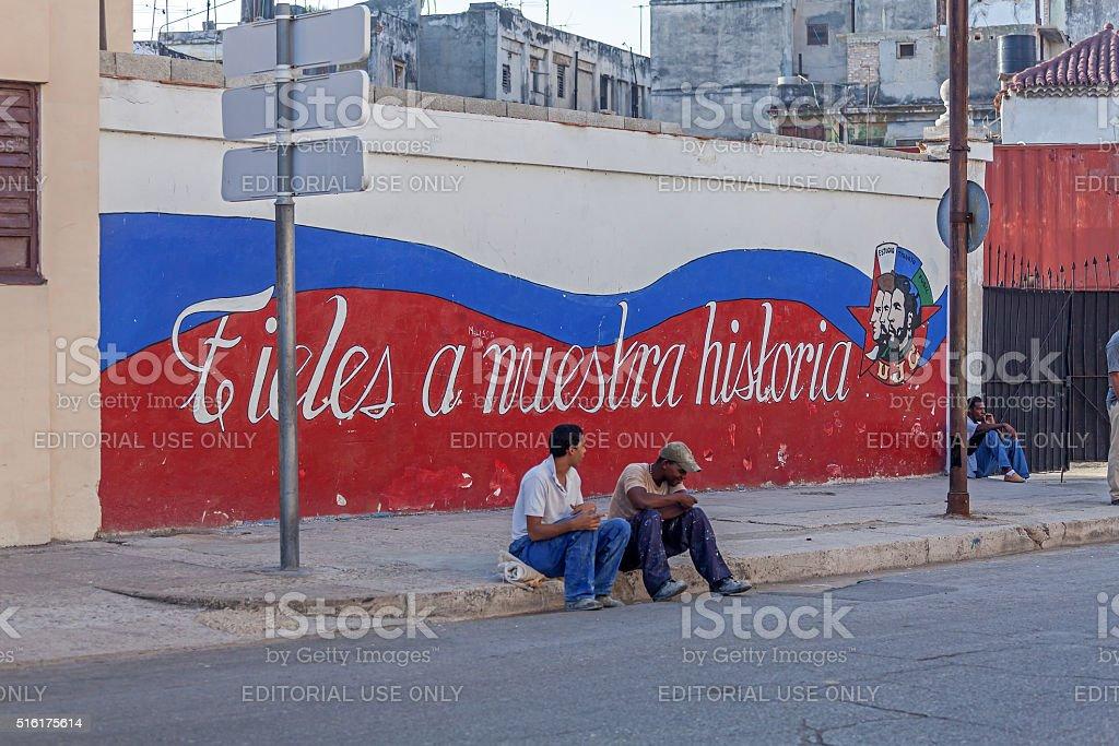 Cuban teenagers sitting near propaganda graffiti stock photo