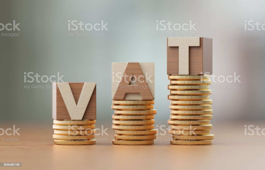 Cube Blocks And Coins Forming VAT Text Over Defocused Background stock photo