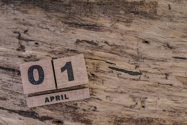 cube calendar for april on wooden background - april fools stock photos and pictures