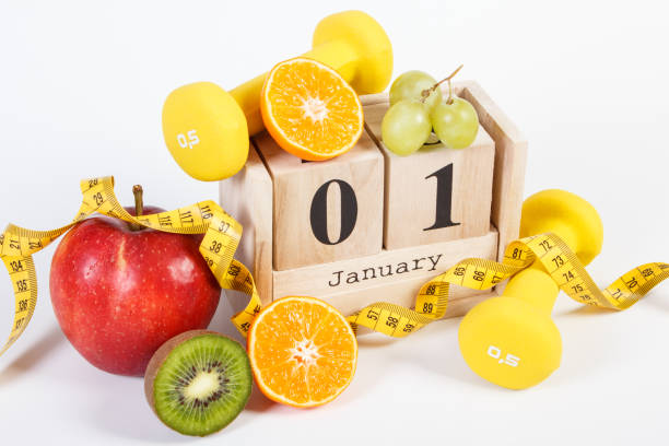 Cube calendar, fruits, dumbbells and tape measure, new years resolutions stock photo